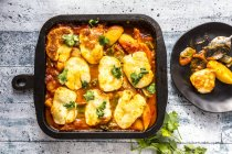 Kartoffelbacken, Kartoffeln, Zuckererbsen, Tomaten, Käse, Petersilie in der Pfanne — Stockfoto