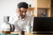 Retrato del hombre de negocios cansado en el escritorio mirando el ordenador portátil — Stock Photo