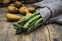 Organic green asparagus wrapped in kitchen towel and organic potatoes on dark wooden background — Stock Photo