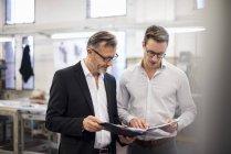 Два бізнесмени в заводі дивлячись на папку — стокове фото