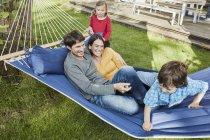 Família feliz que joga no hammock no jardim de sua home — Fotografia de Stock