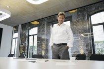 Geschäftsmann betrachtet Dokumente auf Schreibtisch in modernem Büro — Stockfoto