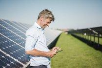 Бизнесмен использует планшет в солнечном парке — стоковое фото