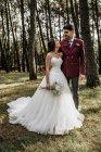 Щасливий наречений і наречена стоячи в лісі — стокове фото