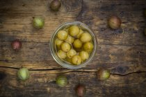 Jar of preserved gooseberries and gooseberries on wooden background — Stock Photo