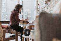 Frau sitzt im Studio und macht sich Notizen — Stockfoto