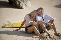 Ласковая пожилая пара с доской для серфинга на пляже — стоковое фото