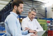 Les hommes d'affaires utilisant la tablette pendant la réunion dans le hall de production — Photo de stock