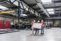 Three men wearing hard hats and safety vests looking at plan on factory shop floor — Stock Photo