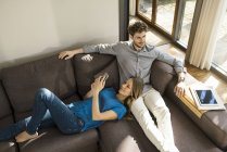 Smiling couple with tablet and smartphone relaxing on sofa at home — Stock Photo