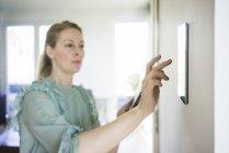 Mulher ajustando tablet digital montado na parede com smartphone — Fotografia de Stock