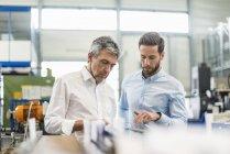 Hommes d'affaires lors d'une réunion avec tablette dans le hall de production — Photo de stock