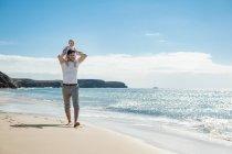 Іспанія, Лансароте, батько проведення маленької дочки на його плечах на пляжі — стокове фото