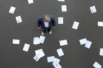 Businessman standing on tarnac surrounded by papers — Stock Photo
