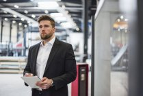 Businessman using tablet on factory shop floor — Stock Photo