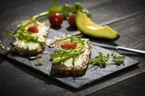 Onion bread with cream cheese, parma ham, avocado, rucola, thyme and tomato — Stock Photo