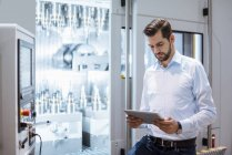 Businessman at machine in factory looking at tablet — Stock Photo