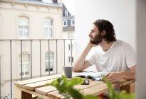 Мечтающий молодой человек сидит с кофейной кружкой и журналом на балконе и смотрит на расстояние — стоковое фото