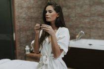 Молода жінка в спа насолоджуючись чашкою чаю — стокове фото