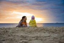 Мать с маленькой дочкой на пляже на закате — стоковое фото