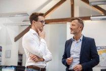 Two businessmen talking in office — Stock Photo
