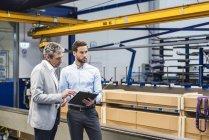 Hommes d'affaires lors d'une réunion avec presse-papiers dans le hall de production — Photo de stock