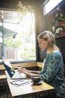 Молода жінка з зеленою сукнею сидить у кафе і працює на ноутбуку. — стокове фото