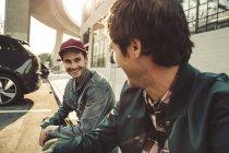 Два улыбающихся юноши сидят на тротуаре — стоковое фото