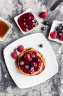 Pancakes with red fruit jelly, maple sirup, raspberries and blueberries — Stock Photo
