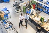 Бізнесмени під час зустрічі з планшетом у виробничому залі, підвищений вигляд — стокове фото