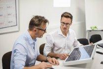 Deux hommes d'affaires examinant le panneau solaire sur le bureau — Photo de stock