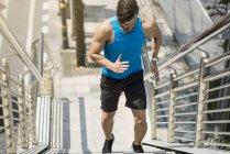 Мужчина в синей футболке бегает по городу наверх — стоковое фото