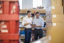 Dois empresários na despensa da fábrica olhando para tablet — Fotografia de Stock
