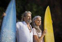 Pareja de ancianos afectuosos con tablas de surf en la playa - foto de stock