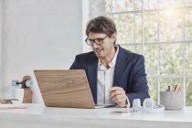 Empresário sorridente usando laptop na mesa — Fotografia de Stock