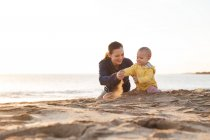 Мама играет с маленькой дочерью на пляже — стоковое фото