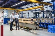Бізнесмени під час зустрічі з буфера обміну у виробничому залі — стокове фото