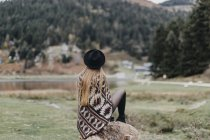 Back view of fashionable young woman wearing hat and poncho and sitting on a rock — Stock Photo