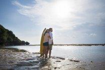 Liebevolles Senioren-Paar mit Surfbrettern am Strand — Stockfoto