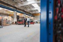 Two men wearing hard hats walking and talking in factory shop floor — Stock Photo