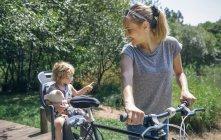 Mère faisant une balade à vélo à travers la campagne avec sa fille dans un siège enfant — Photo de stock
