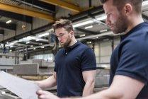 Zwei Männer schauen sich Plan in Fabrik an — Stockfoto