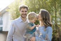 Счастливая семья в саду перед бамбуковыми растениями с поцелуем матери сына — стоковое фото