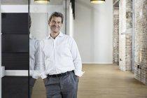 Portrait d'un homme d'affaires souriant appuyé contre une vitre dans un bureau moderne — Photo de stock