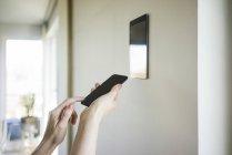 Mani da donna che regolano tablet digitale montato a parete con smartphone — Foto stock