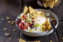 Taco salad bowl with rice, corn, chili con carne, kidney beans, iceberg lettuce, sour cream, nacho chips, tomatoes — Photo de stock
