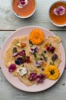 Pancakes with edible flowers, pumpkin flower, Calendula, Chamaemelum nobile, Dianthus, Taraxacum officinale, Viola, Rosmarinus officinalis on bamboo plate and cups of tea — Stock Photo