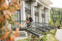 Smiling couple leaving house with bicycles — Stock Photo