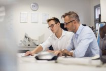 Двое бизнесменов обсуждают план на рабочем столе — стоковое фото