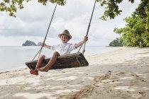 Tailândia, Ko Yao Noi, menino feliz em um balanço na praia — Fotografia de Stock